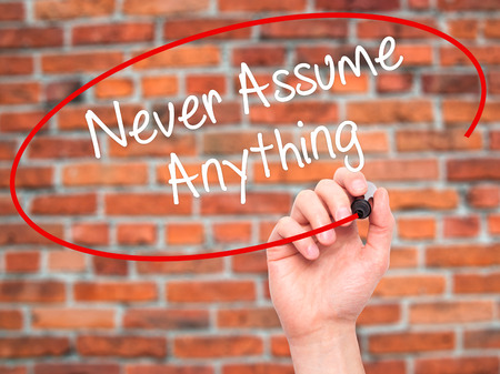 assume: Man Hand writing Never Assume Anything with black marker on visual screen. Isolated on bricks. Business, technology, internet concept. Stock Photo Stock Photo