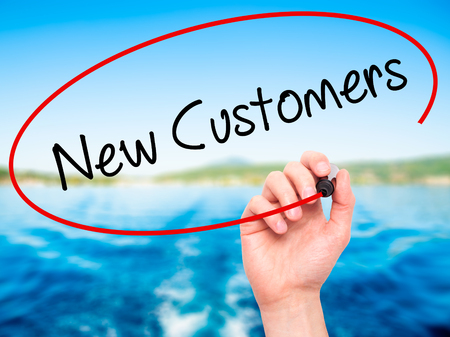 Man Hand writing  New Customers with black marker on visual screen. Isolated on nature. Business, technology, internet concept. Stock Photo Reklamní fotografie