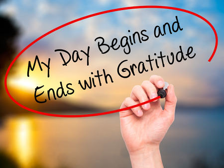 thankfulness: Man Hand writing My Day Begins and Ends with Gratitude with black marker on visual screen. Isolated on nature. Business, technology, internet concept. Stock Photo Stock Photo