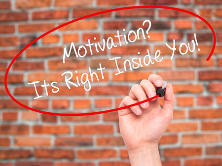 sarcastic: Man Hand writing Motivation? Its Right Inside You!  with black marker on visual screen. Isolated on bricks. Business, technology, internet concept. Stock Photo Stock Photo