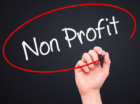 non profit: Man Hand writing Non Profit with black marker on visual screen. Isolated on black. Business, technology, internet concept. Stock Photo Stock Photo