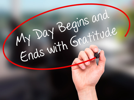 thankfulness: Man Hand writing My Day Begins and Ends with Gratitude with black marker on visual screen. Isolated on office. Business, technology, internet concept. Stock Photo