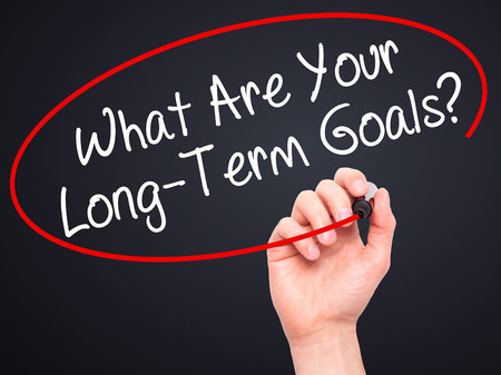 long term goal: Man Hand writing What Are Your Long-Term Goals? with black marker on visual screen. Isolated on black. Business, technology, internet concept. Stock Photo