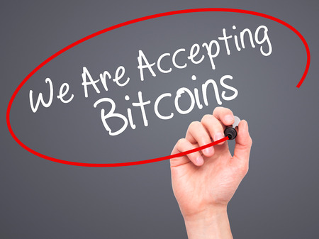 accepting: Man Hand writing We Are Accepting Bitcoins with black marker on visual screen. Isolated on grey. Business, technology, internet concept. Stock Photo