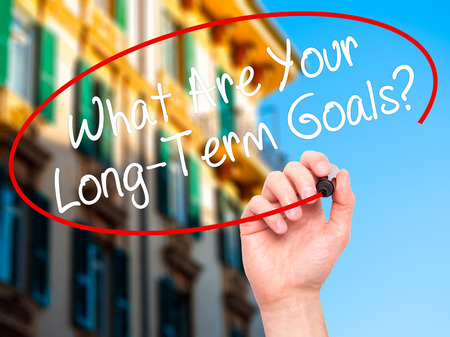 long term goal: Man Hand writing What Are Your Long-Term Goals? with black marker on visual screen. Isolated on city. Business, technology, internet concept. Stock Photo Stock Photo
