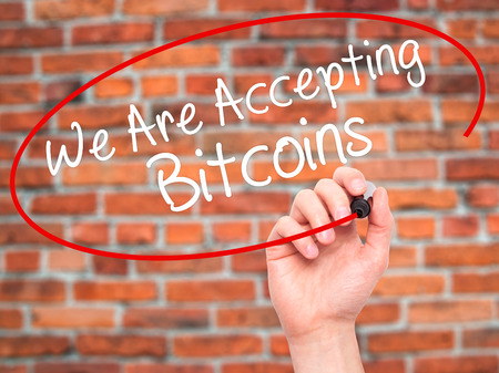 acceptable: Man Hand writing We Are Accepting Bitcoins with black marker on visual screen. Isolated on bricks. Business, technology, internet concept. Stock Photo Stock Photo