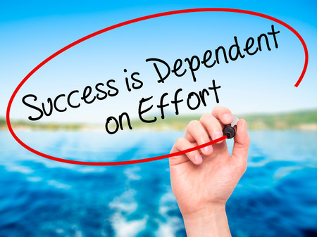 dependent: Man Hand writing Success is Dependent on Effort with black marker on visual screen. Isolated on nature. Business, technology, internet concept. Stock Photo