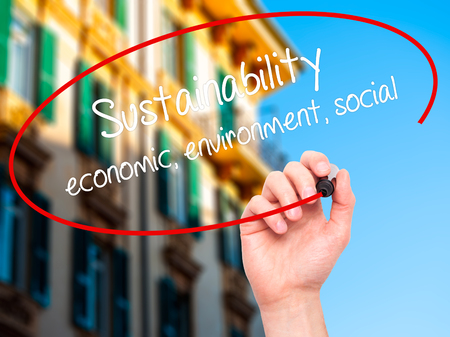 economic theory: Man Hand writing Sustainability  economic, environment, social with black marker on visual screen. Isolated on city. Business, technology, internet concept. Stock Photo