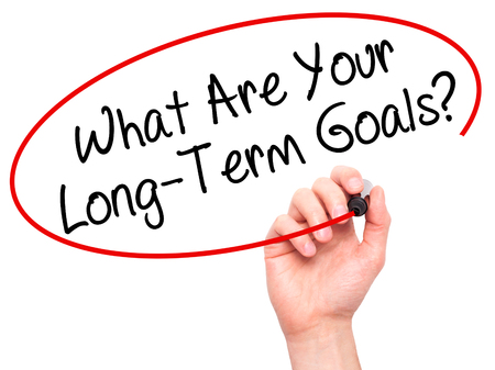 long term goal: Man Hand writing What Are Your Long-Term Goals? with black marker on visual screen. Isolated on white. Business, technology, internet concept. Stock Photo