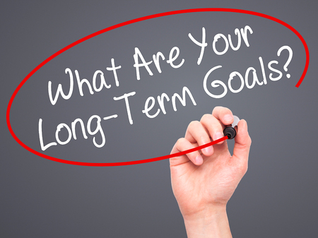 long term goal: Man Hand writing What Are Your Long-Term Goals? with black marker on visual screen. Isolated on grey. Business, technology, internet concept. Stock Photo