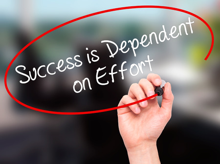 dependent: Man Hand writing Success is Dependent on Effort with black marker on visual screen. Isolated on office. Business, technology, internet concept. Stock Photo
