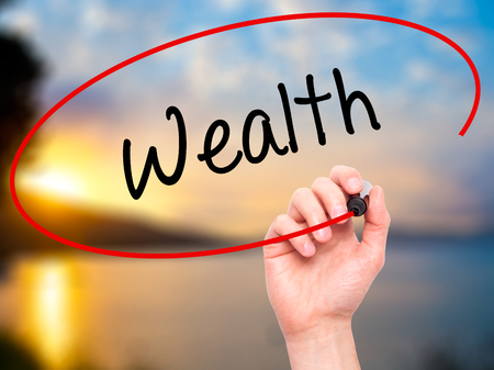 Man Hand writing Wealth with black marker on visual screen. Isolated on background. Business, technology, internet concept. Stock Photo