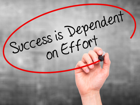 dependent: Man Hand writing Success is Dependent on Effort with black marker on visual screen. Isolated on grey. Business, technology, internet concept. Stock Photo