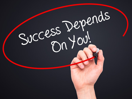 depends: Man Hand writing Success Depends On You! with black marker on visual screen. Isolated on black. Business, technology, internet concept. Stock Photo Stock Photo