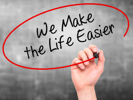 easier: Man Hand writing We Make the Life Easier with black marker on visual screen. Isolated on grey. Business, technology, internet concept. Stock Photo Stock Photo