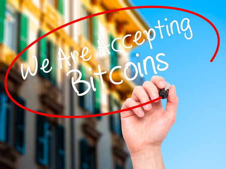accepting: Man Hand writing We Are Accepting Bitcoins with black marker on visual screen. Isolated on city. Business, technology, internet concept. Stock Photo Stock Photo