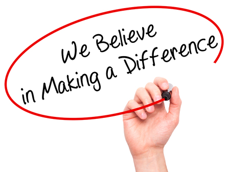 difference: Man Hand writing We Believe in Making a Difference with black marker on visual screen. Isolated on background. Business, technology, internet concept. Stock Photo