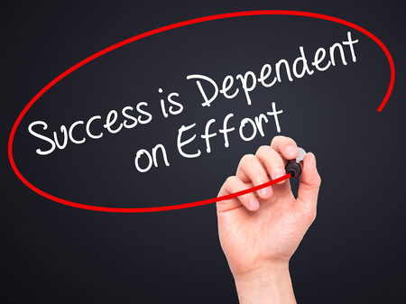 dependent: Man Hand writing Success is Dependent on Effort with black marker on visual screen. Isolated on black. Business, technology, internet concept. Stock Photo