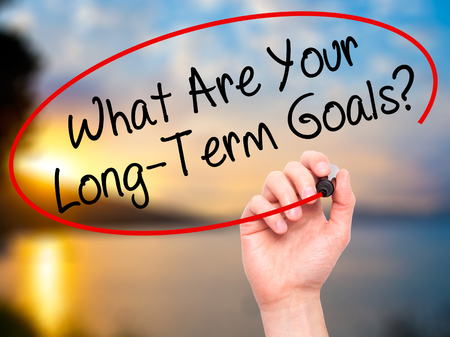 long term goal: Man Hand writing What Are Your Long-Term Goals? with black marker on visual screen. Isolated on nature. Business, technology, internet concept. Stock Photo