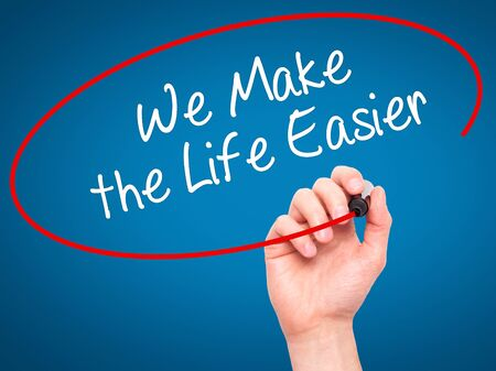easier: Man Hand writing We Make the Life Easier with black marker on visual screen. Isolated on blue. Business, technology, internet concept. Stock Photo Stock Photo