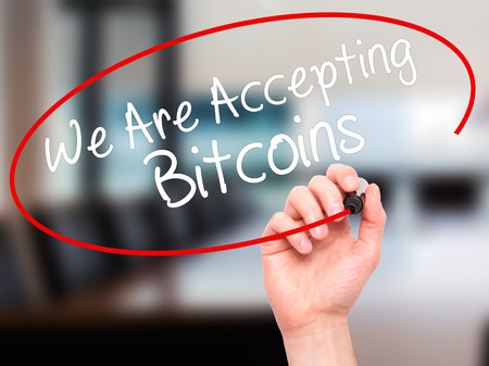 accepting: Man Hand writing We Are Accepting Bitcoins with black marker on visual screen. Isolated on office. Business, technology, internet concept. Stock Photo