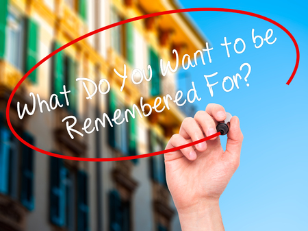 remembered: Man Hand writing What Do You Want to be Remembered For? with black marker on visual screen. Isolated on city. Business, technology, internet concept. Stock Photo