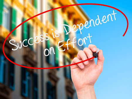 dependent: Man Hand writing Success is Dependent on Effort with black marker on visual screen. Isolated on city. Business, technology, internet concept. Stock Photo Stock Photo