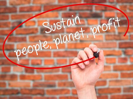 sustain: Man Hand writing Sustain, people, planet, profit with black marker on visual screen. Isolated on bricks. Business, technology, internet concept. Stock Photo