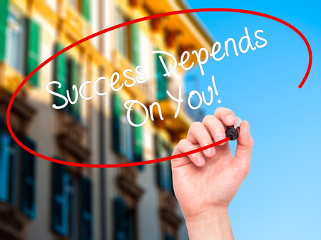 depends: Man Hand writing Success Depends On You! with black marker on visual screen. Isolated on city. Business, technology, internet concept. Stock Photo Stock Photo