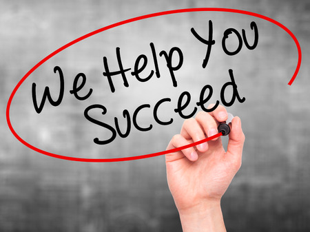 succeed: Man Hand writing We Help You Succeed with black marker on visual screen. Isolated on grey. Business, technology, internet concept. Stock Photo