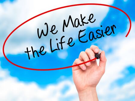 easier: Man Hand writing We Make the Life Easier with black marker on visual screen. Isolated on sky. Business, technology, internet concept. Stock Photo Stock Photo
