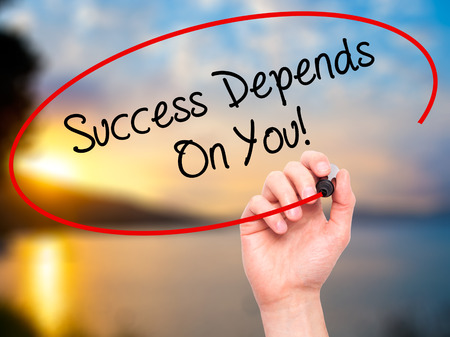 depends: Man Hand writing Success Depends On You! with black marker on visual screen. Isolated on nature. Business, technology, internet concept. Stock Photo