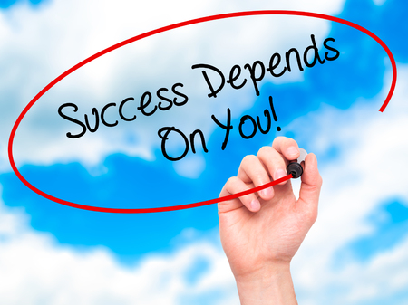 depends: Man Hand writing Success Depends On You! with black marker on visual screen. Isolated on sky. Business, technology, internet concept. Stock Photo Stock Photo