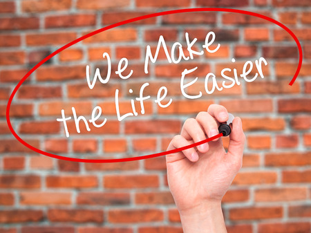 easier: Man Hand writing We Make the Life Easier with black marker on visual screen. Isolated on bricks. Business, technology, internet concept. Stock Photo