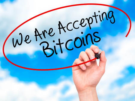 accepting: Man Hand writing We Are Accepting Bitcoins with black marker on visual screen. Isolated on sky. Business, technology, internet concept. Stock Photo