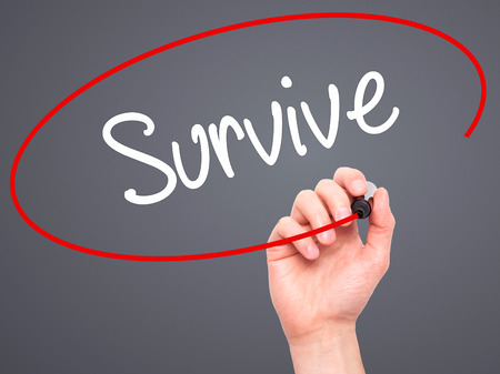 persevere: Man Hand writing Survive with black marker on visual screen. Isolated on background. Business, technology, internet concept. Stock Photo