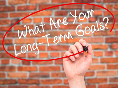 long term goal: Man Hand writing What Are Your Long-Term Goals? with black marker on visual screen. Isolated on bricks. Business, technology, internet concept. Stock Photo