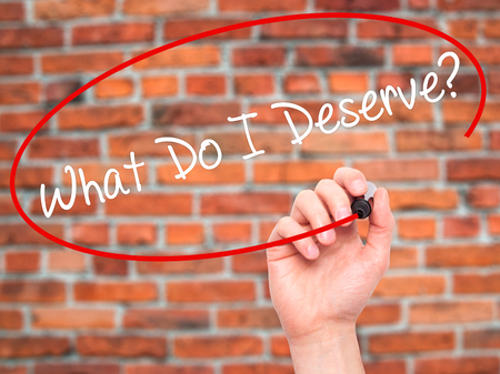 Man Hand writing What Do I Deserve? with black marker on visual screen. Isolated on background. Business, technology, internet concept. Stock Photo