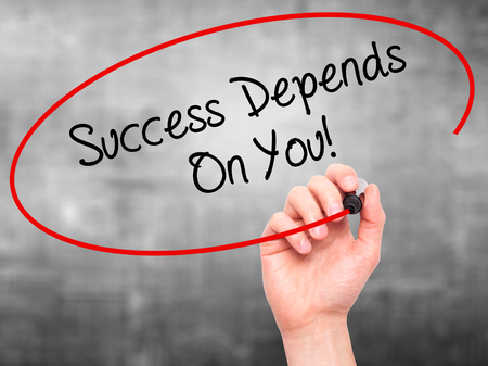 depends: Man Hand writing Success Depends On You! with black marker on visual screen. Isolated on grey. Business, technology, internet concept. Stock Photo Stock Photo