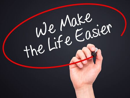 easier: Man Hand writing We Make the Life Easier with black marker on visual screen. Isolated on black. Business, technology, internet concept. Stock Photo Stock Photo