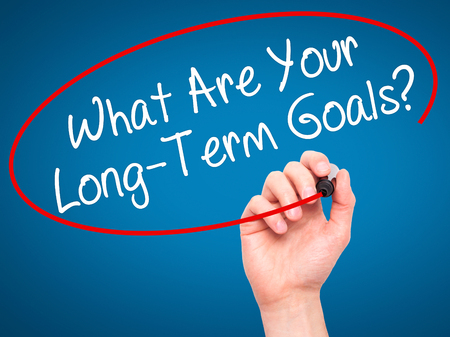 long term goal: Man Hand writing What Are Your Long-Term Goals? with black marker on visual screen. Isolated on blue. Business, technology, internet concept. Stock Photo