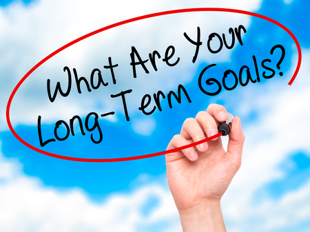 longterm: Man Hand writing What Are Your Long-Term Goals? with black marker on visual screen. Isolated on sky. Business, technology, internet concept. Stock Photo