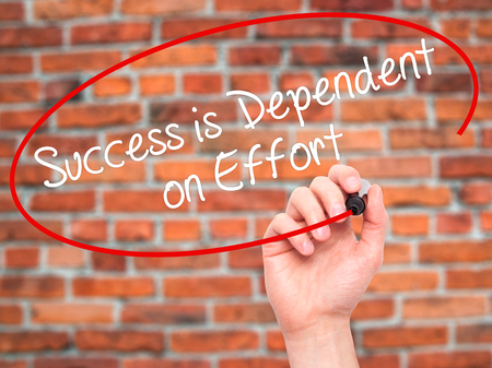 dependent: Man Hand writing Success is Dependent on Effort with black marker on visual screen. Isolated on bricks. Business, technology, internet concept. Stock Photo