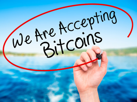 accepting: Man Hand writing We Are Accepting Bitcoins with black marker on visual screen. Isolated on nature. Business, technology, internet concept. Stock Photo Stock Photo