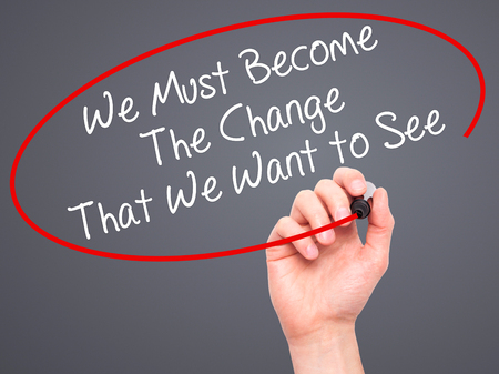 become: Man Hand writing We Must Become The Change That We Want to See with black marker on visual screen. Isolated on background. Business, technology, internet concept. Stock Photo
