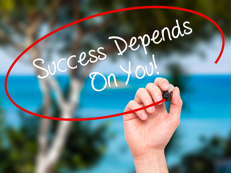 depend: Man Hand writing Success Depends On You! with black marker on visual screen. Isolated on nature. Business, technology, internet concept. Stock Photo
