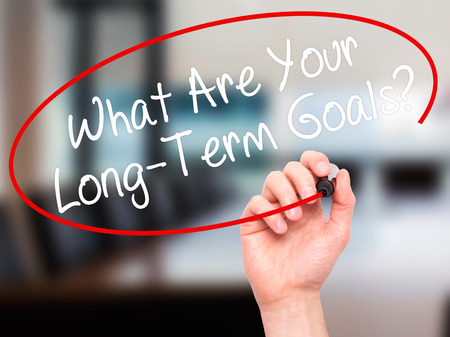 longterm: Man Hand writing What Are Your Long-Term Goals? with black marker on visual screen. Isolated on office. Business, technology, internet concept. Stock Photo