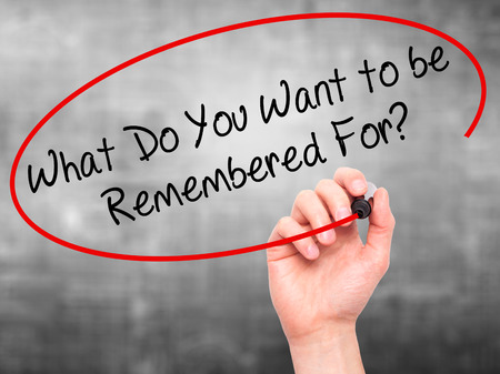 remembered: Man Hand writing What Do You Want to be Remembered For? with black marker on visual screen. Isolated on grey. Business, technology, internet concept. Stock Photo
