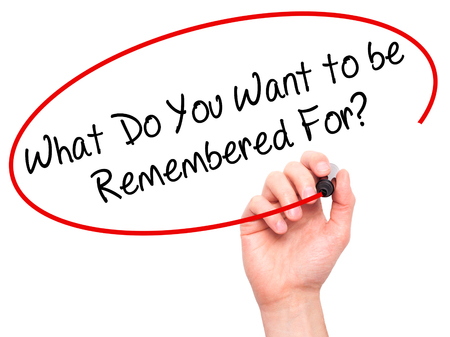 remembered: Man Hand writing What Do You Want to be Remembered For? with black marker on visual screen. Isolated on white. Business, technology, internet concept. Stock Photo