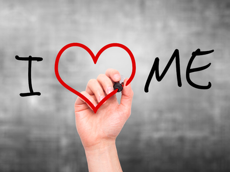 egoistic: Man hand writing I Love Me on visual screen. Love, family, internet concept. Isolated on grey. Stock Photo